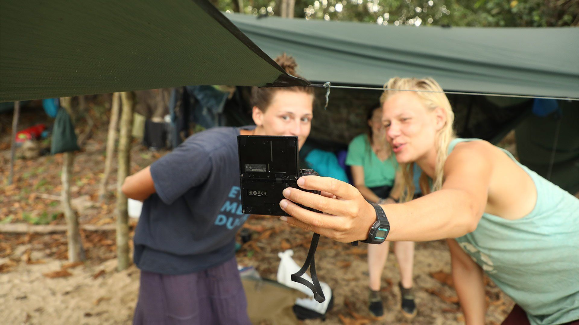 Laura and Ness Knight use a Canon PowerShot G7 X Mark II to film themselves in front of a tent in the jungle, inside which Pip Stewart is sitting.